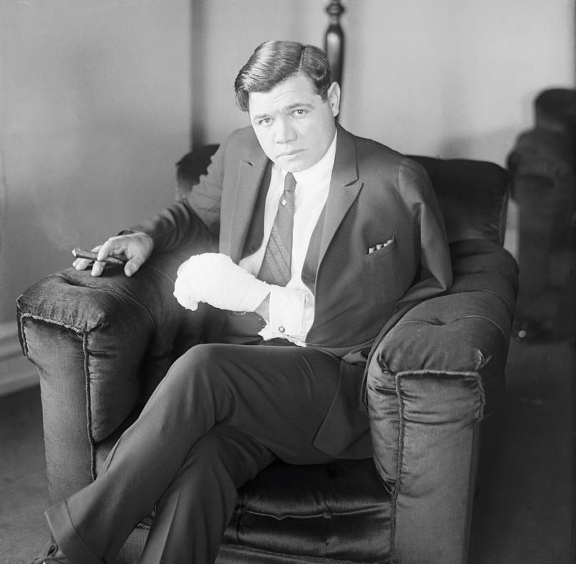 Babe Ruth in a chair smoking