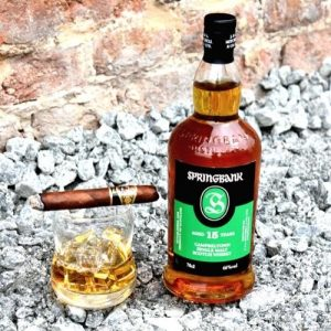 bottle of Springbank 15 Year next to a glass with rum and a cigar on the top